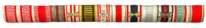 Figure 11: a ribbon bar with  13 ribbons the seventh of which is the red cross decoration with attached 1st class insignia. Image from the author's archive.