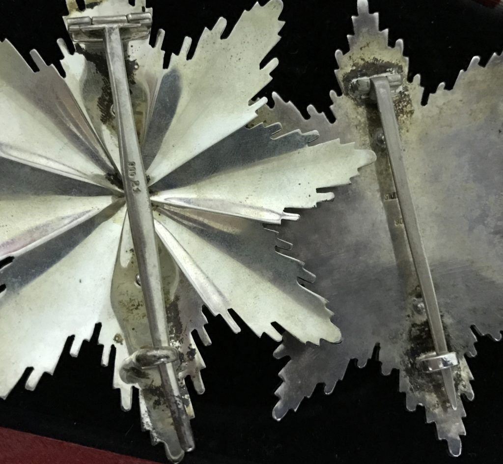 Figure 3: needle and reverse design comparison between 1st type to the right and one of the 2nd types to the left. Two Grand Cross stars.