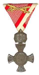 Figure 11: Iron Merit Cross with crown on war ribbon with swords. Image from the author's archive.